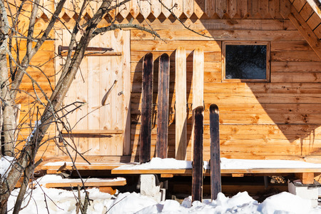 wide hunter skis in front of wooden cottage in sunny winter day in russian village in Smolensk region of Russia 免版税图像