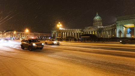 view of Kazansky Cathedral on snow-covered Nevsky Prospect street in night snowfall in Saint Petersburg city in March