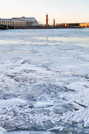 ice-bound Neva river and Spit of Vasilyevsky Island with Rostral Column and Old Stock Exchange building in Saint Petersburg city in March evening
