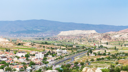 GOREME, TURKEY - MAY 5, 2018: panoramic view of mountain valley with Goreme town and road in spring. Goreme is town in Cappadocia, in the Nevsehir Province in Central Anatolia of Turkey Editorial