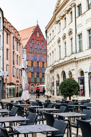AUGSBURG, GERMANY - MAY 20, 2018: empty outdoor cafe and people on street Philippine-Welser-Strasse in Augsburg town in rain. Augsburg is a city in Swabia, Bavaria, it is third oldest city in Germany Editorial