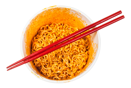 red chopsticks over cup with prepared spicy instant noodles isolated on white background Stock Photo