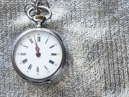 two minutes to twelve o'clock on retro pocket watch on silver textile background