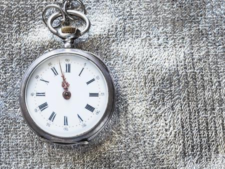 dos minutos para las doce en punto en el reloj de bolsillo retro sobre fondo textil plateado