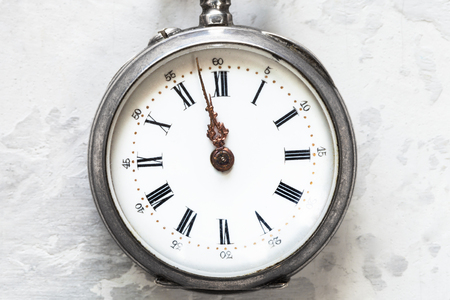 retro pocket watch on white concrete background close up