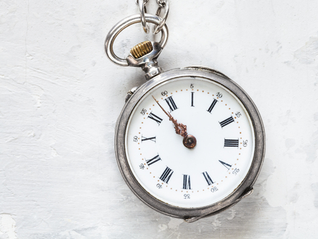 two minutes to twelve o'clock on antique pocket watch on white concrete background