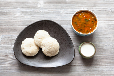 Indian cuisine - Idli Sambar steamed rice and urad bean dal dumplings served with sambar and chutney sauces on gray wooden board