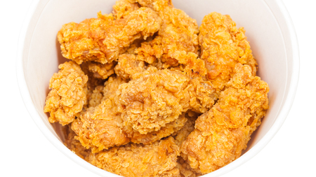 many crispy batter deep-fried chicken wings in paper bucket isolated on white background 写真素材