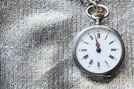 two minutes to twelve o'clock on antique pocket watch on silver textile background Archivio Fotografico