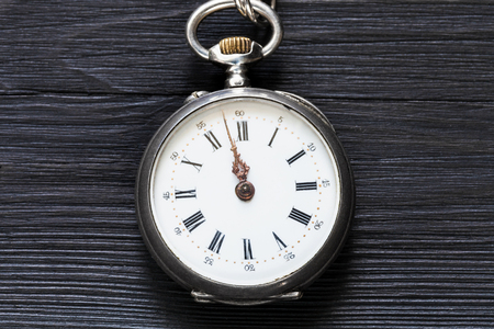 two minutes to twelve o'clock on vintage pocket watch on black wooden background Фото со стока