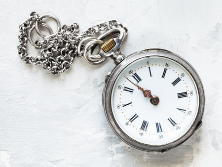 two minutes to twelve o'clock on old pocket watch with chain on white concrete background