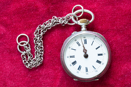 vintage silver pocket watch with chain on red velvet background