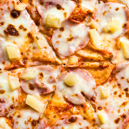 filling of Hawaiian pizza with ham and pineapple close up