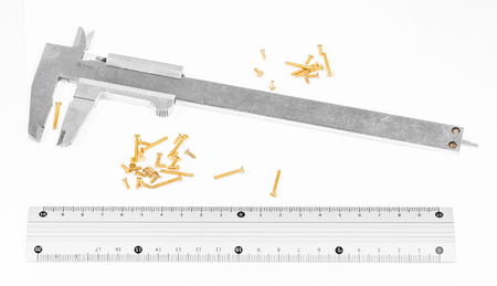 old steel calipers, metallic ruler and many of brass screws on white background Stock Photo