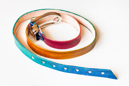narrow varicoloured leather belt on white background