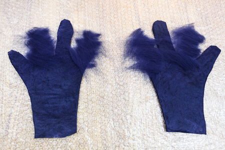 workshop of hand making a fleece gloves from blue Merino sheep wool using wet felting process - partly shaped with cutting pattern wet gloves with new layer of fibers on fingers