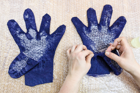 workshop of hand making a fleece gloves from blue Merino sheep wool using wet felting process - craftsman forms the finger of glove with the cutting pattern