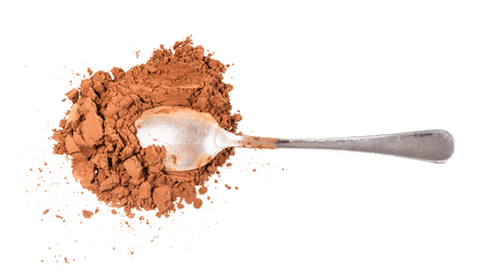 top view of spoon in pile of ground carob powder isolated on white background Фото со стока