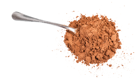 top view of pile of ground carob powder with steel spoon isolated on white background Foto de archivo