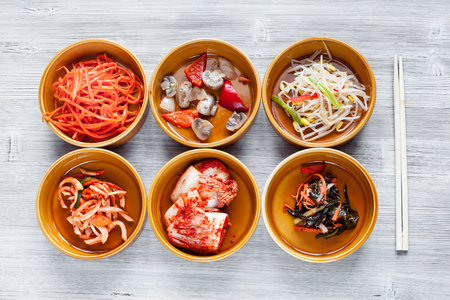 korean cuisine - top view of various side dishes (Banchan or Panchan) in ceramic bowls with chopsticks on gray table Stock Photo