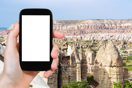 travel concept - tourist photographs of fairy chimney rocks in mountain valley of Goreme National Park in Cappadocia in Turkey on smartphone with empty cutout screen with blank place for advertising