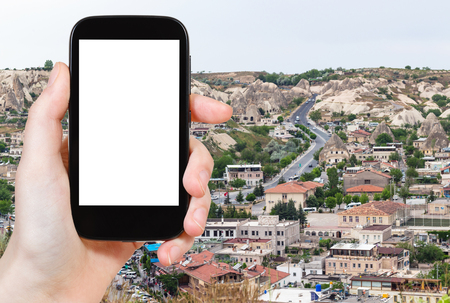 travel concept - tourist photographs of road in modern residential district in Goreme town in spring in Turkey on smartphone with empty cutout screen with blank place for advertising