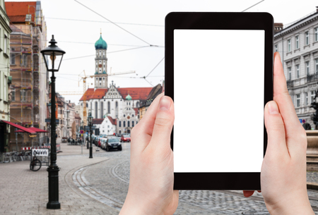 travel concept - tourist photographs of Maximilianstrasse and view of Basilica SS Ulrich and St Afra in Augsburg town in Germany on smartphone with empty cutout screen with blank place for advertising