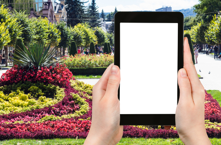 travel concept - tourist photographs of flowerbed on Kurortnyy bulvar in Kislovodsk town in Caucasian Mineral Waters region of Russia on smartphone with cut out screen with blank place for advertising Фото со стока