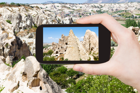 travel concept - tourist photographs of ancient rock-cut monastic settlement near Goreme town in Cappadocia on smartphone in Turkey in spring Banco de Imagens