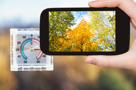 travel concept - tourist photographs yellow trees and outdoor thermometer on home window in hot autumn day on smartphone in Moscow, Russia