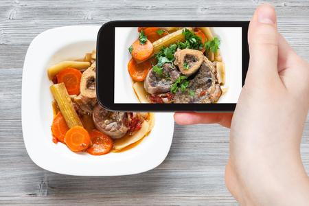 travel concept - visitor photographs of italian dish Ossobuco in white plate on smartphone