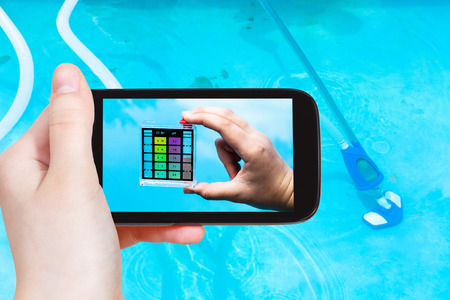 travel concept - tourist photographs of a hand holding the pH indicator for measure the acidity of water in a outdoor swimming pool on smartphone
