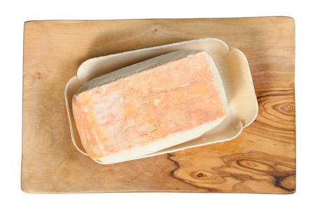 top view of piece of local italian Taleggio cheese from cow's full milk on olive wood cutting board isolated on white background