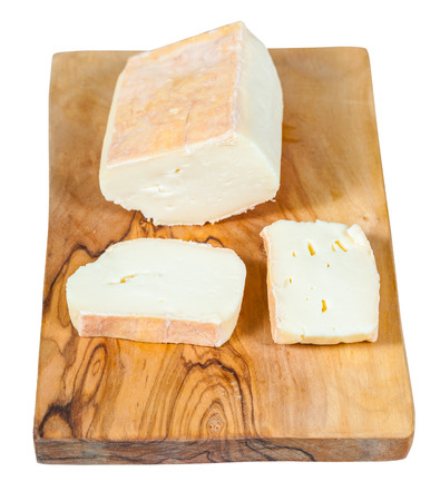 sliced local italian Taleggio cheese from cows full milk on olive wood cutting board isolated on white background 스톡 콘텐츠