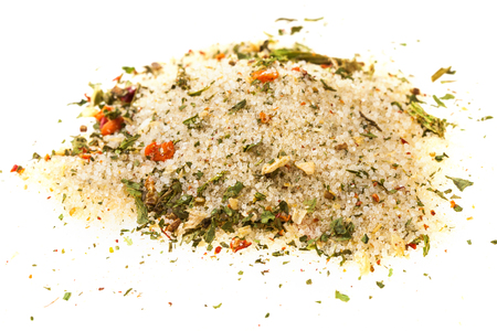 handful of seasoned salt with dried vegetables and flavours on white background