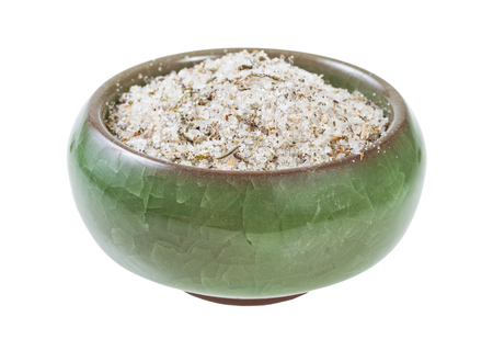 side view of ceramic salt cellar with seasoned salt with spices and dried herbs isolated on white background