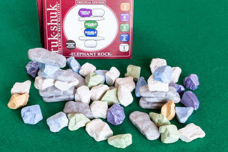 MOSCOW, RUSSIA - APRIL 2, 2019: pile from various stones and box of Ruk Shuk, the Game of Rock Balancing, on green baize table. The game was designed by Malcolm Bisiker and published in 2006