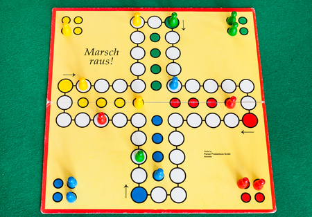 MOSCOW, RUSSIA - APRIL 2, 2019: gameboard of Marsch Raus ! board game on green baize table. This board game is Cross and circle game, an adaptation of the medieval Indian game Pachisi