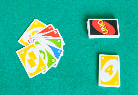 MOSCOW, RUSSIA - APRIL 3, 2019: card decks of UNO game on green baize table. Uno is shedding-type card game developed in 1971 by Merle Robbins, the game has become a Mattel brand since 1992