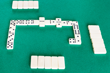 playfield of dominoes board game with white tiles on green baize table