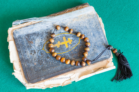 worry beads above old orthodox psalm book on green baize table Banco de Imagens