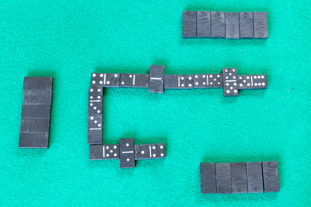 top view of gameplay of dominoes board game with black tiles on green baize table Foto de archivo