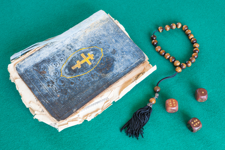 old psalm book, worry beads and three wooden dices on green baize