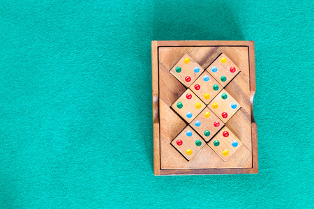 top view of wooden box with puzzle on green baize table with copyspace