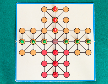 top view of cross solitaire board game on green baize table. The first mention of peg solitaire game can be identified in France in 1697