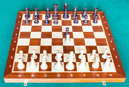 view from white side of wooden chessboard with first chess pawn moves on green baize table