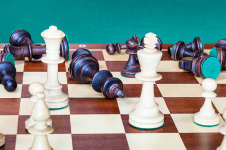 business concept - falling black side (except pawn) and wining white side of chess