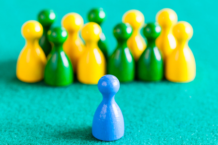 concept scene - one blue pawn in front of other color pawns on green baize table. Focus on the blue pawn Banque d'images