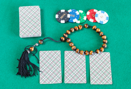 top view of card decks, casino tokens and worry beads on green baize table Stock Photo