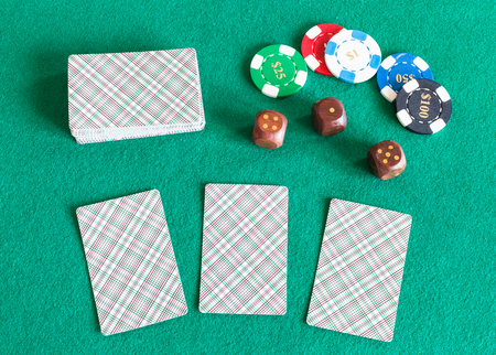 top view of card decks, casino tokens and wooden dices on green baize table